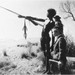 A photo from the movie Walkabout which shows an aboriginal teen pointing out something with a stick to two British children