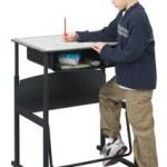 Photo of child standing at his desk writing