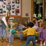 Photo of young children in classroom with joined hands in a circle with teacher