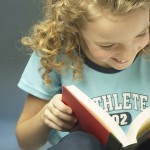Photo of young girl reading a book