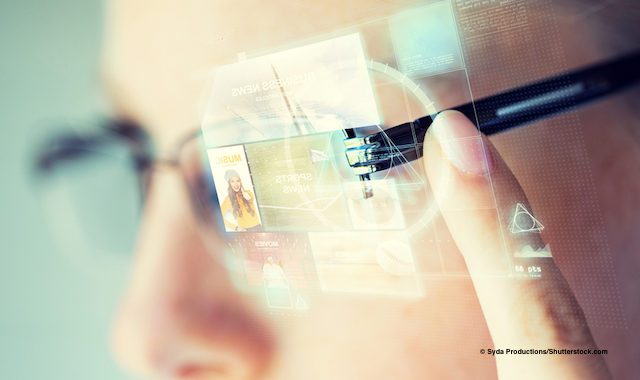 Close-up photo of person with glasses showing computer images over the lens