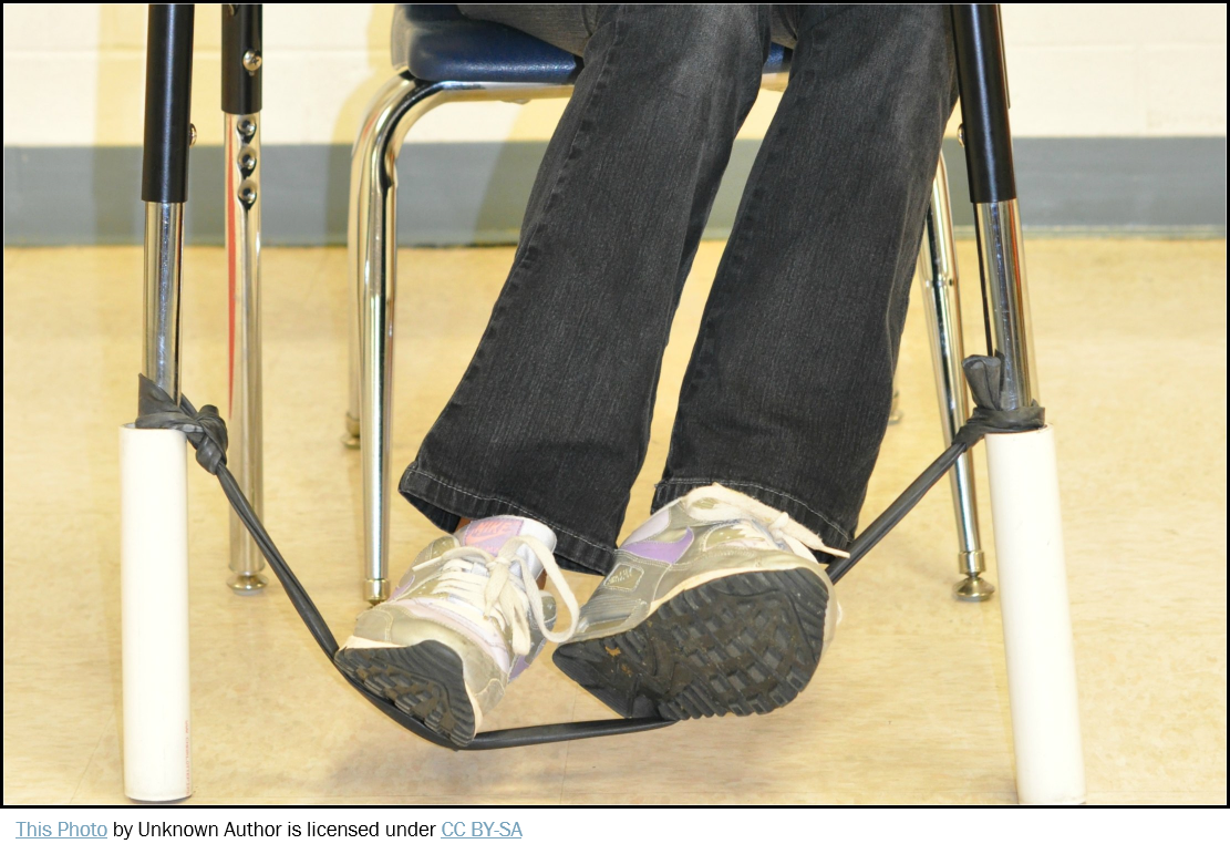 Photo showing bottom half of student at desk with feet on elastic bouncy band