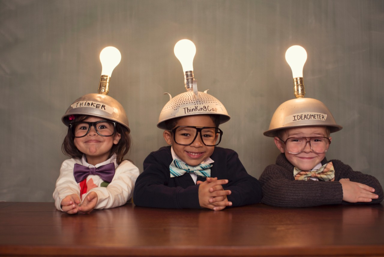 Photo of three young children with metal bowls and light bulbs on their heads