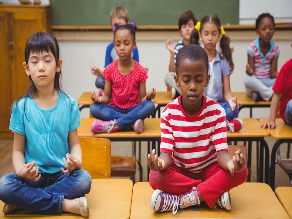 Picture of young students sitting on desk and meditating